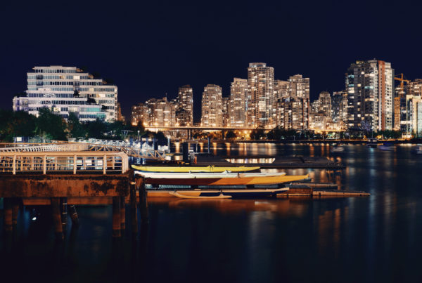 Vancouver city night view with buildings and boat in bay. Photo by dengsongquan | Canva.