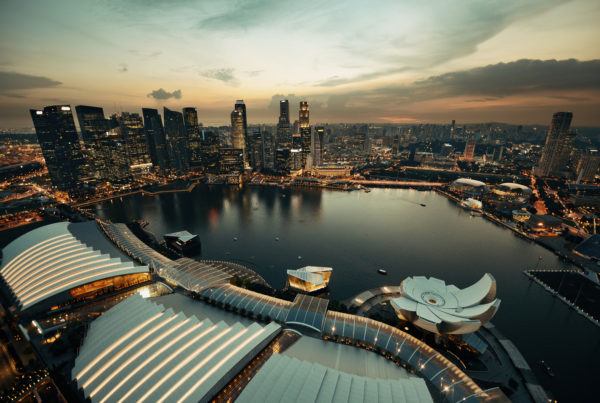 Singapore rooftop view of Marina Bay with urban skyscrapers at sunset. Photo by dengsongquan | Canva.