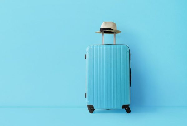 Image of suitcase with hat on handle in blue room--ready to travel. Photo by Nastco | Canva.