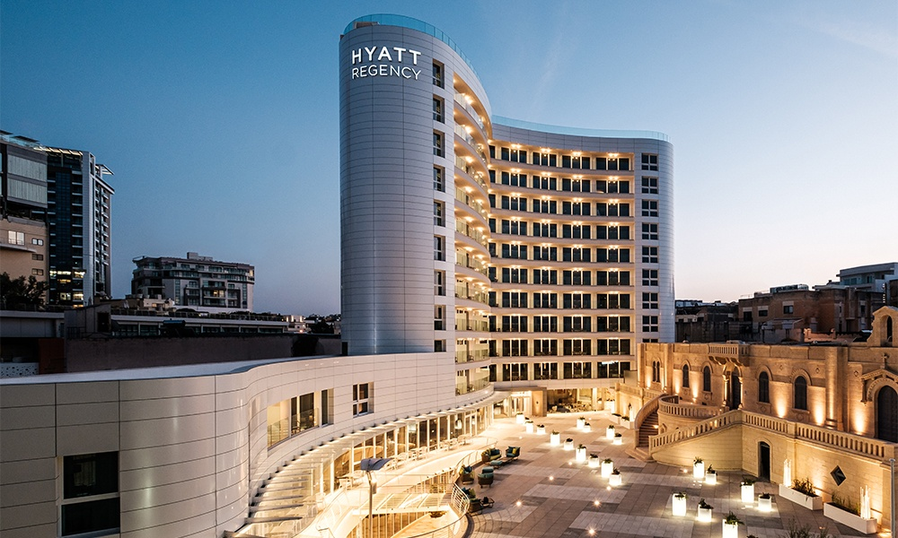 Hyatt Regency Malta is the first Hyatt brand property to open on the Mediterranean island. Image of the hotel's exterior at twilight is by Brian Grech.