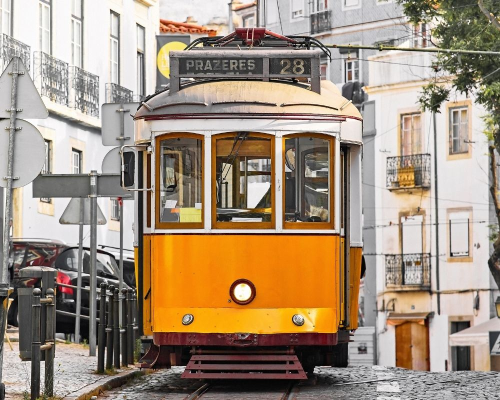Lisbon is known for its retro yellow trams, which can be rented for private tours of the city. Photo by Yasonya/Canva.
