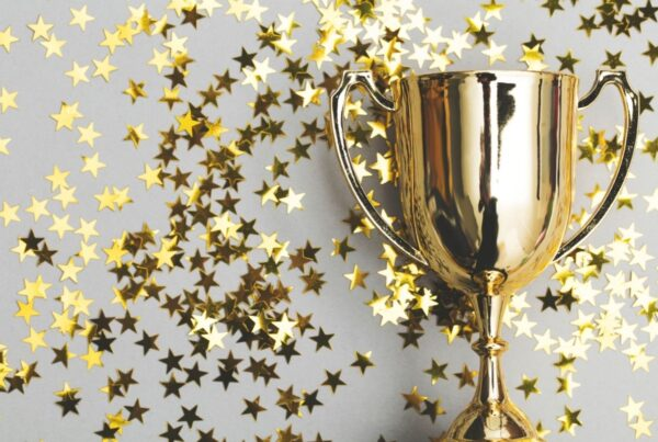 The EIC has announced the winners of its Global Recognition Awards. Image here shows a gold winner's cup on background of gold stars. Photo by inkpot | Canva.