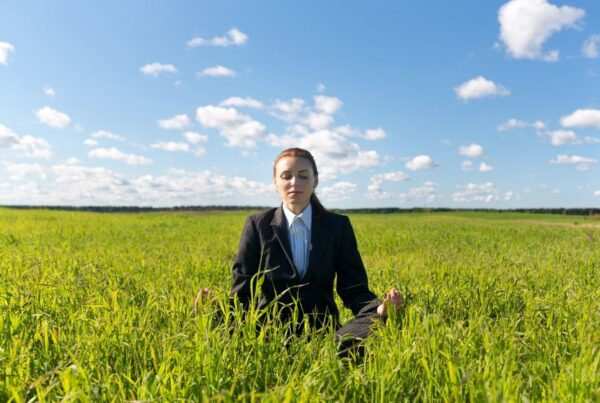 Wellness at MICE events is the topic of the newest study from the Incentive Research Foundation. Photo here shows a businesswoman meditating in a green field. Photo by 97 from Getty Images Signature | Canva.